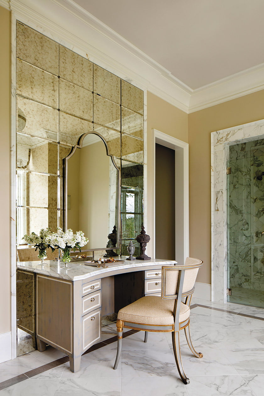 A small makeup table against a mirrored background in the master bath.