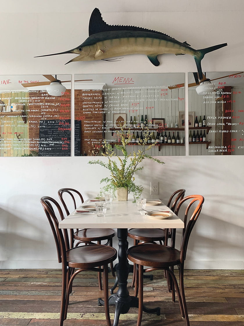 A stuffed marlin presides over mirrors printed with the menu in Le Comptoir du Vin's farmhouse-style dining room