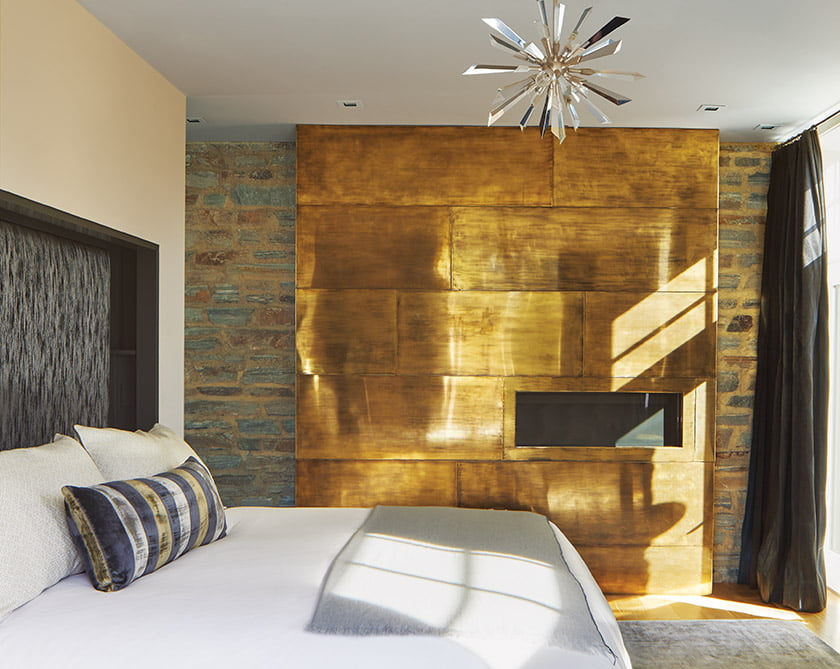 The first-floor master bedroom features an antiqued-brass fireplace wall in the bedroom. © Anice Hoachlander