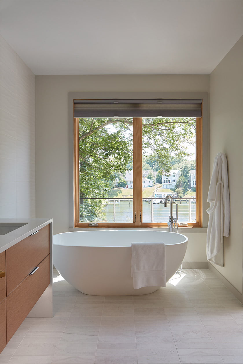 In the master bath, a Signature Hardware soaking tub enjoys water views.