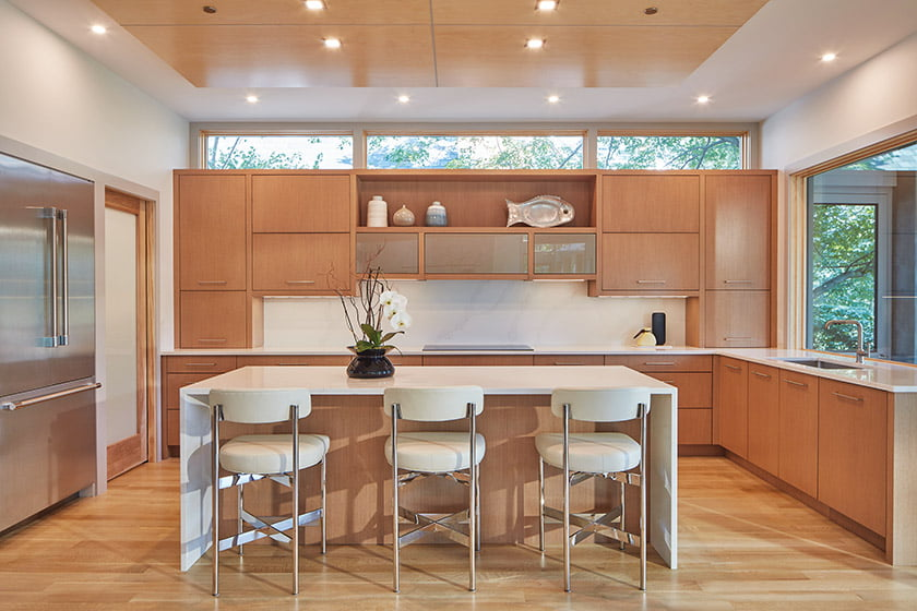 The kitchen sports custom Wood-Mode cabinetry, quartz waterfall counters and stools from Mitchell Gold + Bob Williams.