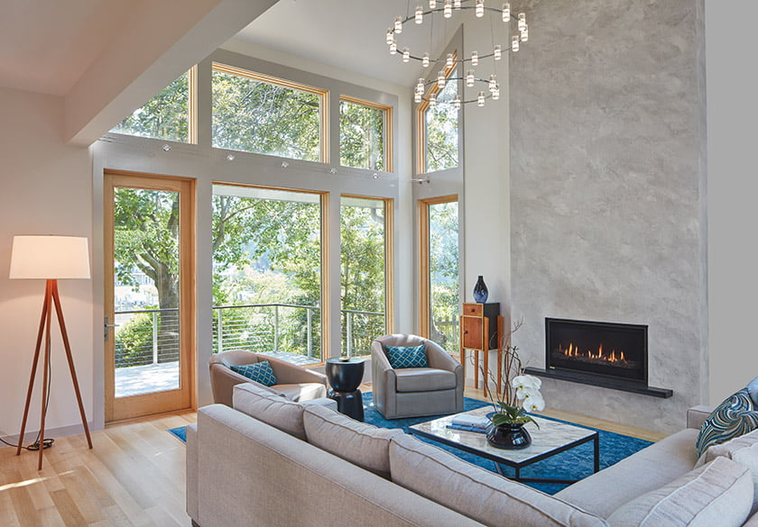 A floor-to-vaulted-ceiling fireplace clad in lime plaster creates a dramatic focal point in the living area.