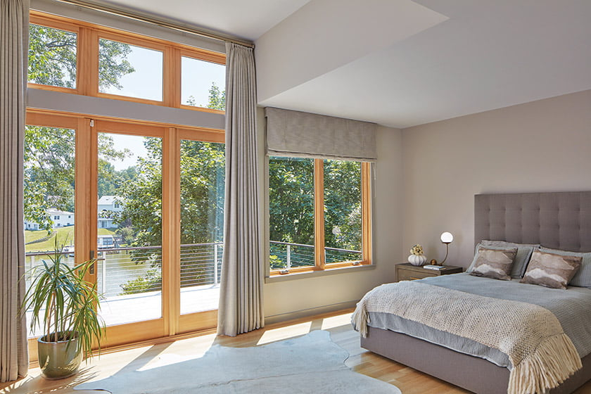 The master bedroom boasts its own balcony; window treatments by Window Expressions soften the space.