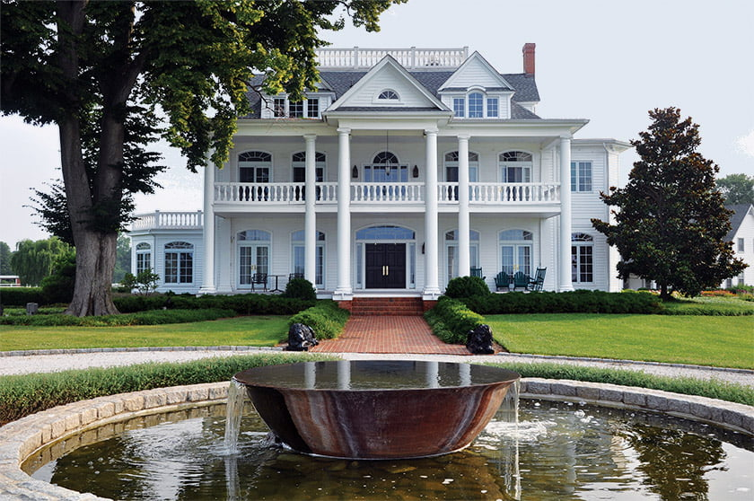 A fountain centered on an old sugar kettle aligns with the formal entrance to the 200-year-old residence.