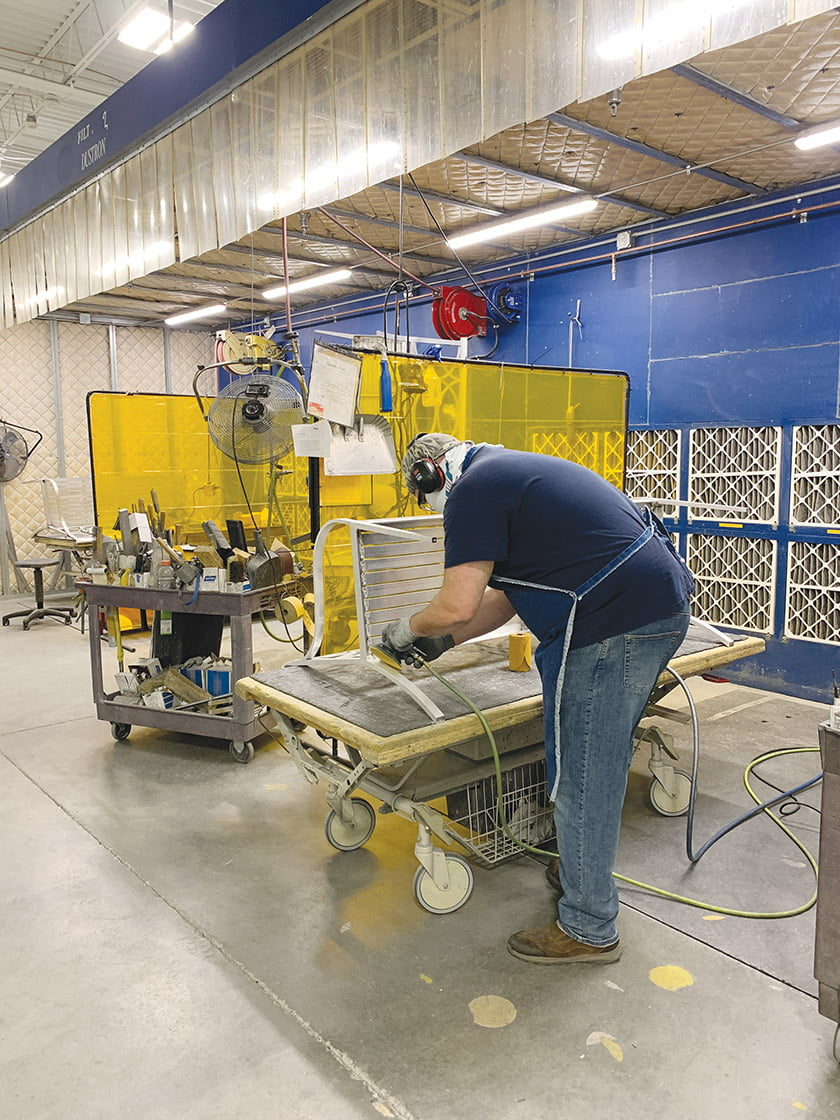 After a bench has been welded, a craftsperson sands every surface by hand.