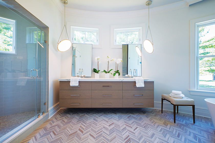 The spa-like master bath boasts a heated floor covered in herringbone-patterned porcelain tile.