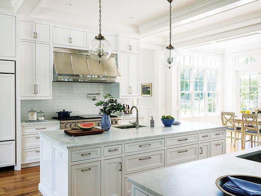 The kitchen marries marble countertops, a subway-tile backsplash and custom Lyndon Heath cabinets.