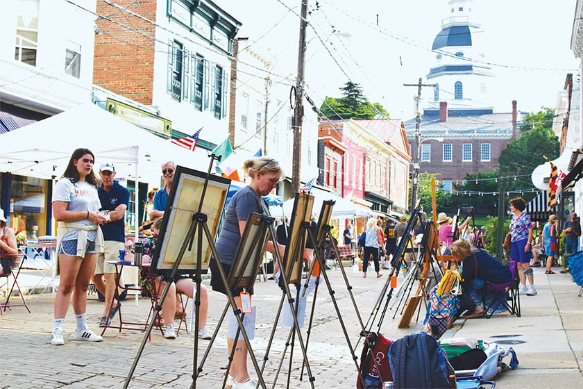 Plein-air artists demonstrate their skills while the State House looms at the end of the cobblestone street.