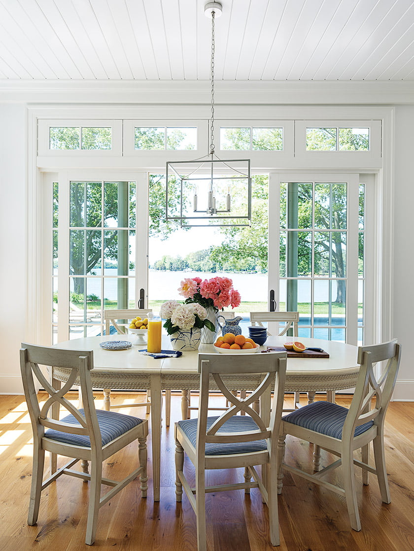 In the casual dining area, French sliders frame a view of the pool, with Island Creek beyond.