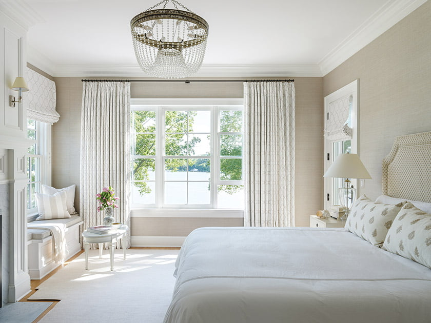 A woven-texture Cowtan & Tout wall covering  envelops the master bedroom. Matouk linens cover the bed.