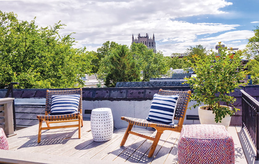 The rooftop deck, furnished with woven chairs and ottomans, captures views of the National Cathedral.