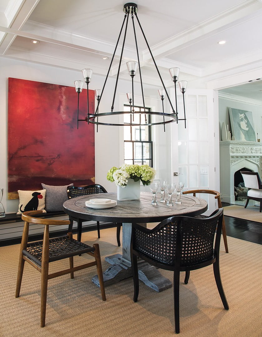 An RH chandelier presides above the custom, reclaimed-wood table in the renovated dining room.