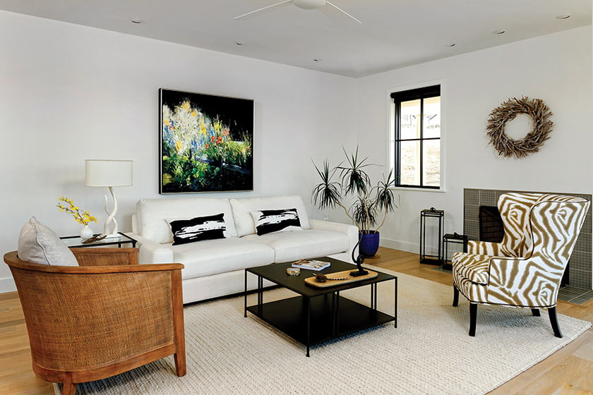 The cozy living room features a bold painting by local artist Ruthie Windsor Mann.