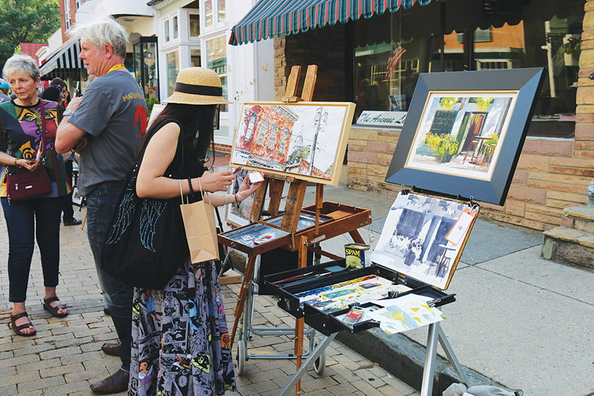 Shoppers peruse plein-air artworks, on display during Art on the Avenue.