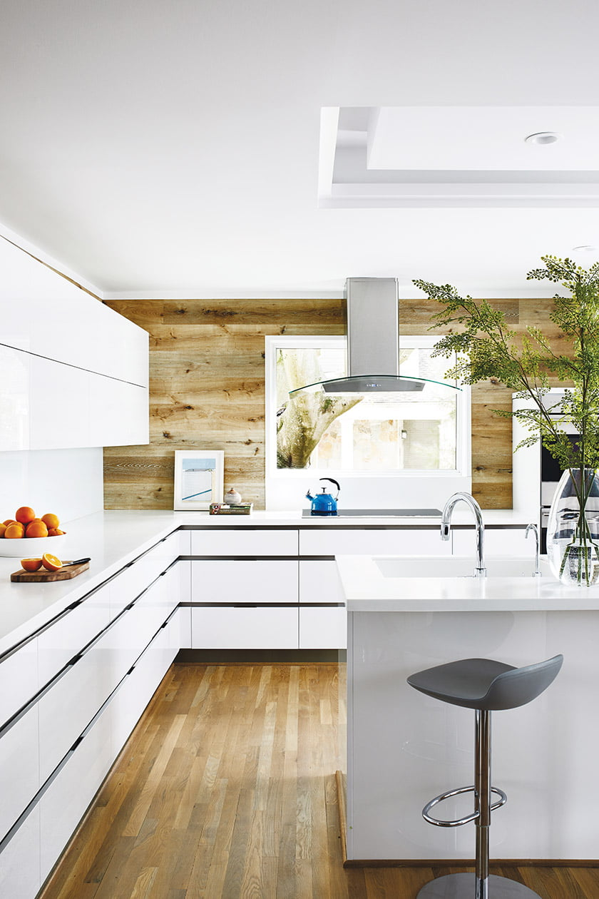 The kitchen combines white-gloss cabinetry with a rustic-looking backsplash.