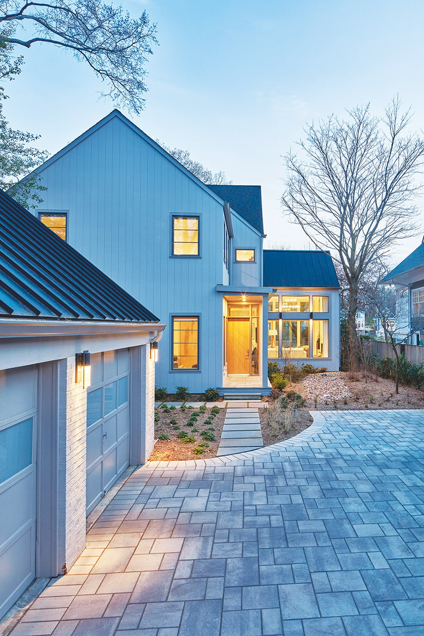 A driveway of pavers leads to the garage, beyond which the house beckons; the glassed-in living area extends to the right.