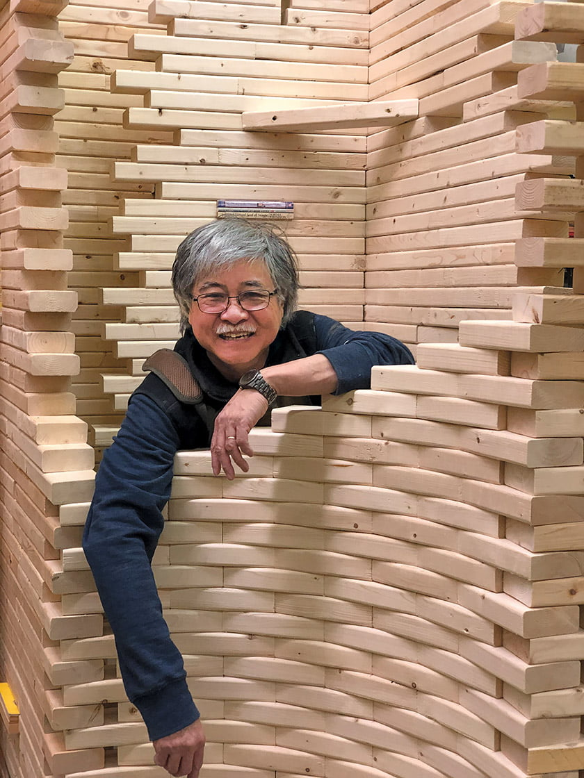 "The artist poses with ""Maze of Knowledge,"" a commission interweaving books and bricks of pine."