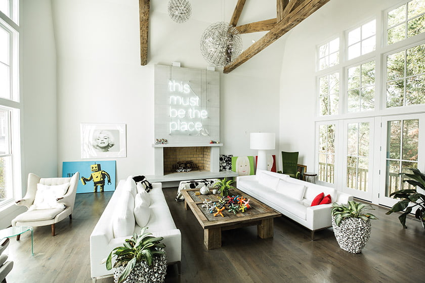 In an Arlington renovation, a two-story great room boasts reclaimed beams and a precast-concrete fireplace.