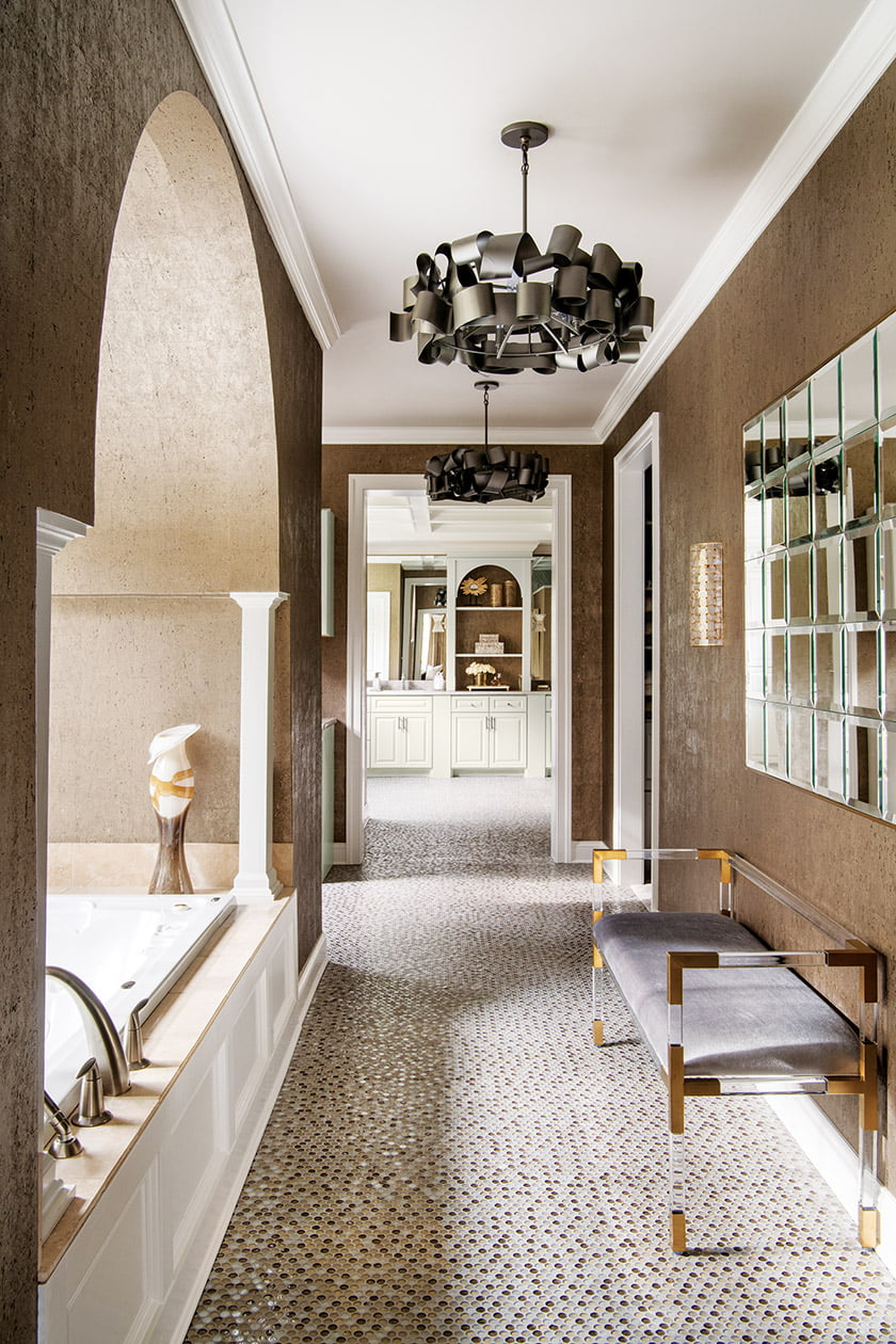 The passage houses a soaking tub; penny tiles in an array of textures and tones pave the floors.