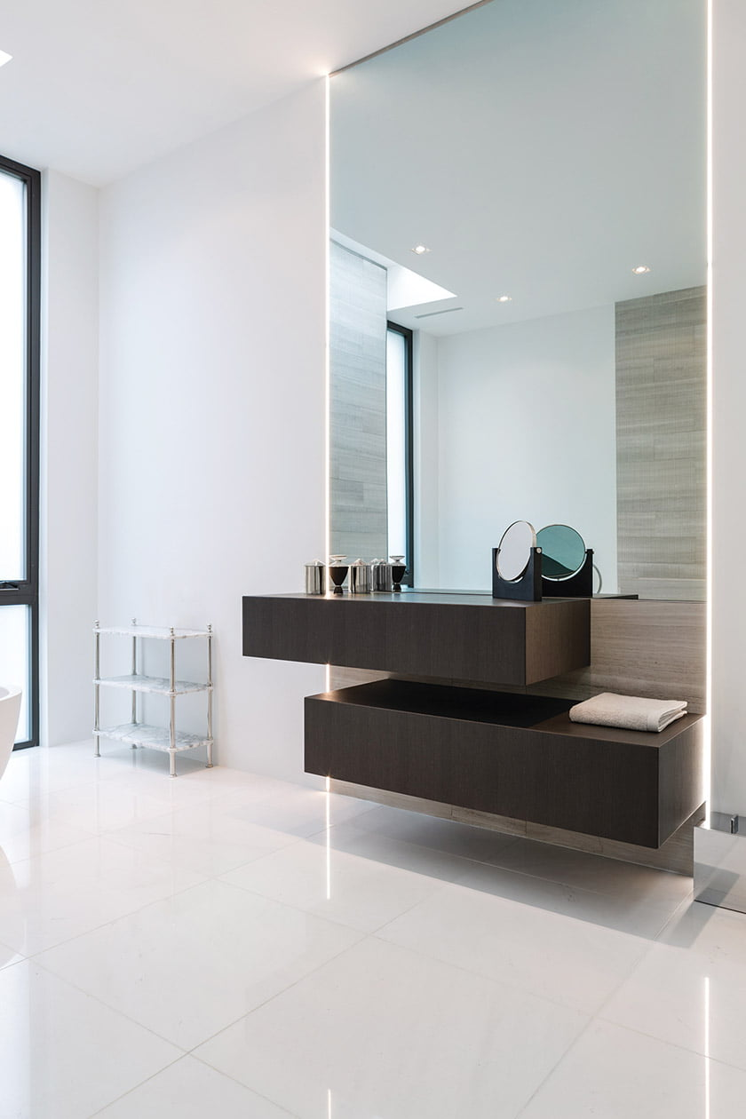 The mirror above the floating vanity conceals a built-in TV.