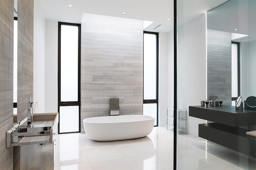 A Boffi vessel tub creates a focal point, flanked by tall windows frosted for privacy.