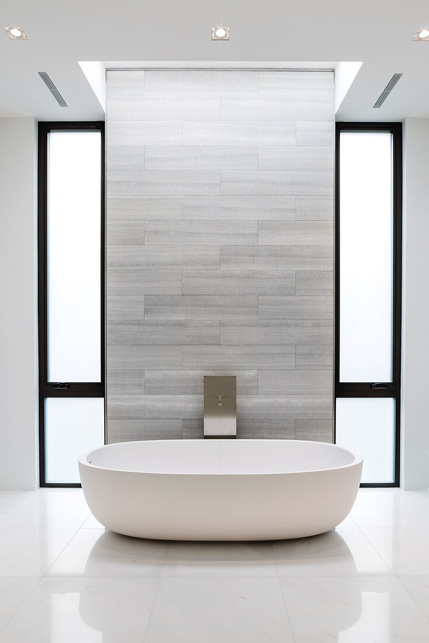 A skylight above the tub bathes the room in natural light.