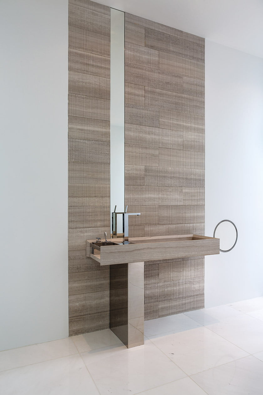 The vessel sink and limestone panels are by Salvatori.