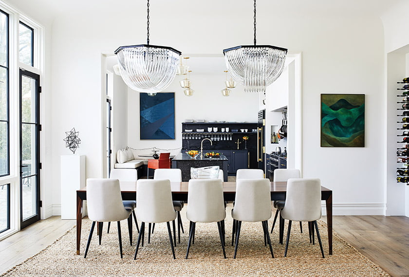 Sparkling, oversized chandeliers from Sunpan hang over a table for 10 in the dining room.