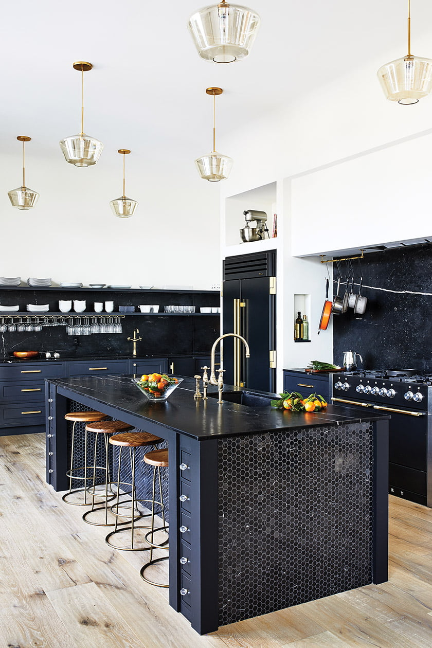 Furnishings and materials establish a glamorous mood in the kitchen with black marble and mosaics on the island.