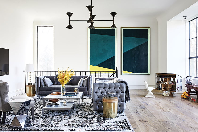 In the family room, gray-velvet sofas from Tov Furniture share center stage with a dollhouse and paintings by Greer.