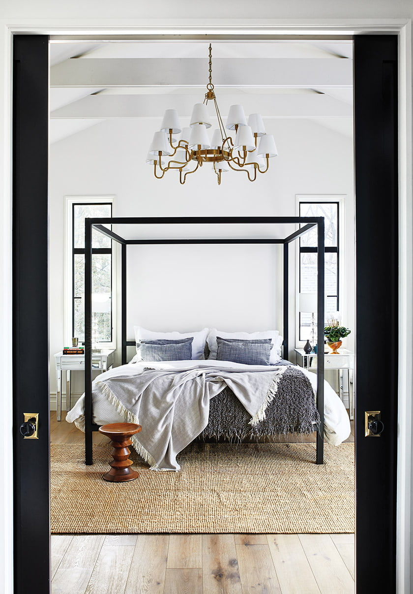 Greer's black-and-white-palette continues in the second-floor master suite, where pocket doors enclose the bedroom.