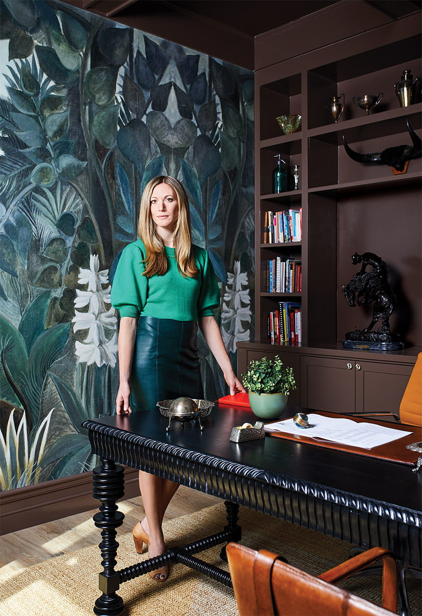 Carmel Greer poses in her husband's study, where a custom wall covering replicates a painting by Henri Rousseau.