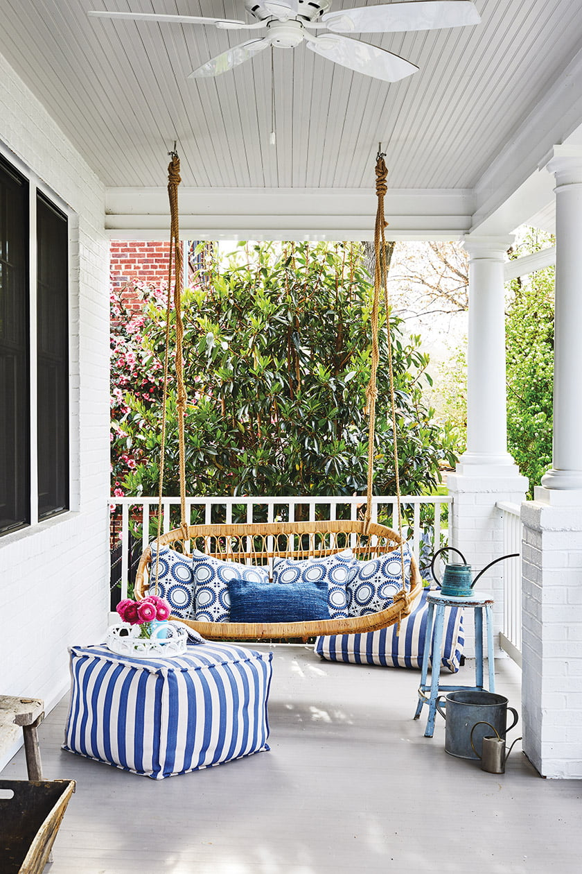 A Serena & Lily porch swing and cheerful Annie Selke striped ottomans embellish the front porch.