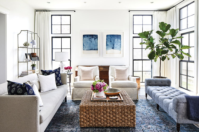 The airy, light-filled family room introduces shades of blue through dip-dye art by John Robshaw and an antique rug.