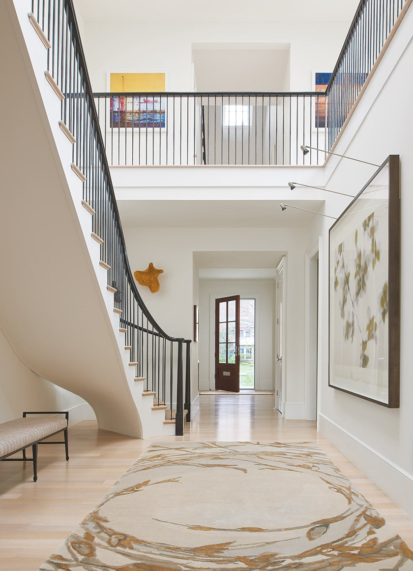 In the entry, a sculptural floating staircase leads to the upstairs gallery.