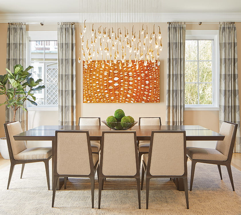 Artful lighting by Ochre and a painting by Kevin Kepple bring drama and vibrancy to the dining room.