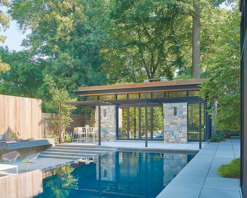 The 800-square-foot pool house is a stone, steel and glass structure equipped with a fireplace and kitchen.
