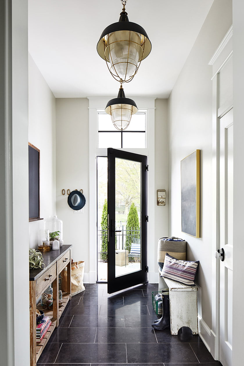 The mudroom is enlivened by a honed-bluestone tile floor and Visual Comfort pendants.