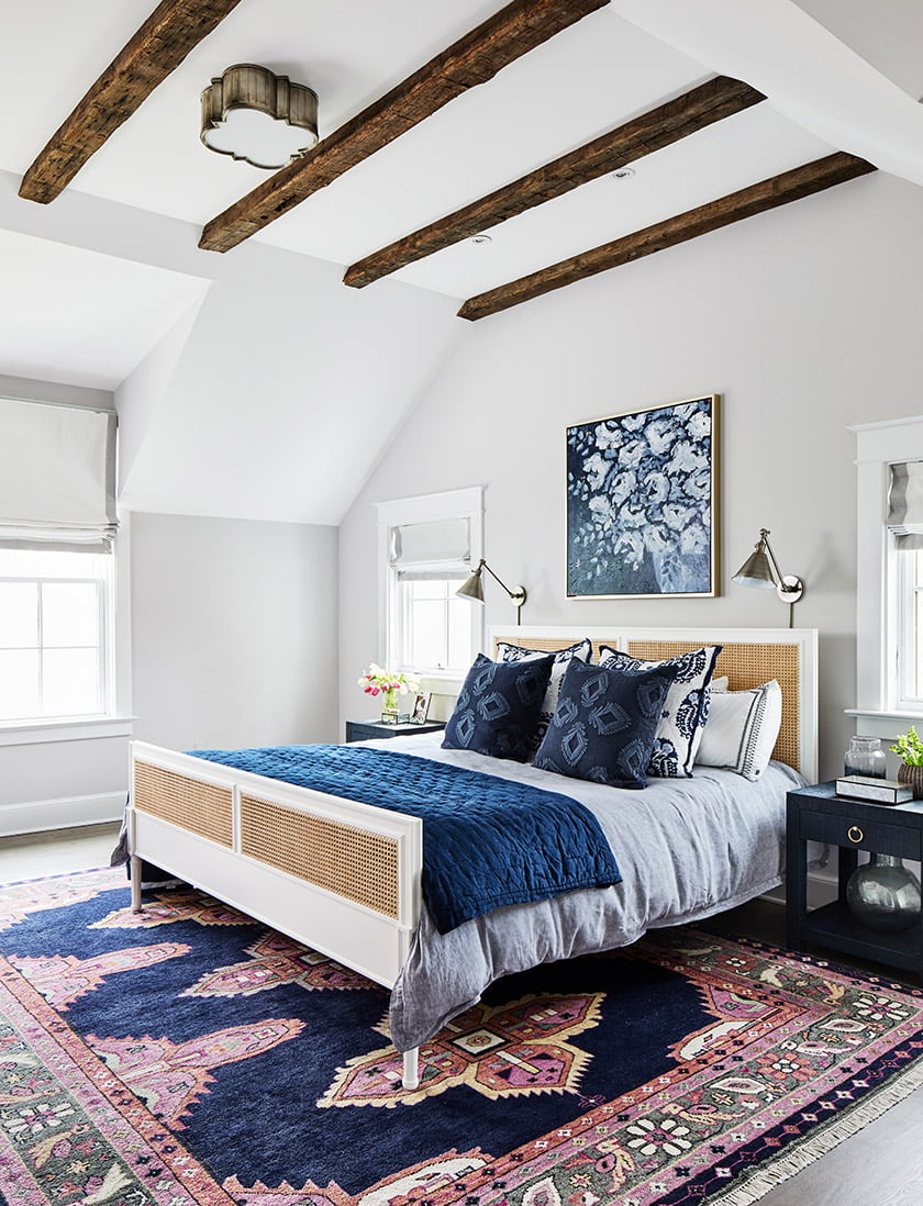 A Caitlin Wilson rug grounds the master bedroom, where reclaimed beams sound a rustic note.