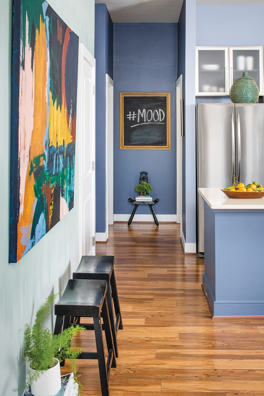 The living area is painted Copen Blue and the kitchen in Solitude and Distance—all by Sherwin Williams.