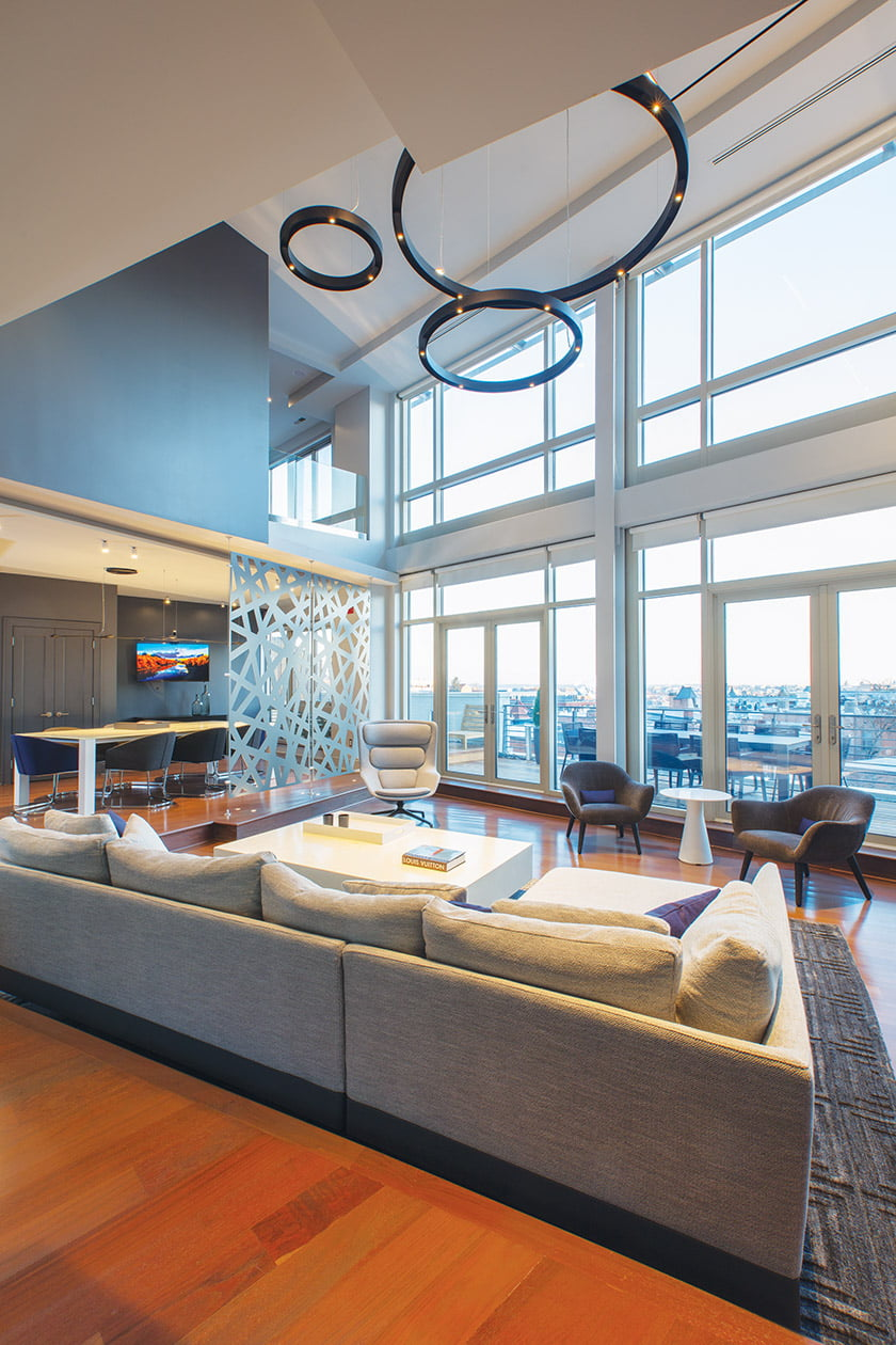 In a transformed Adams Morgan penthouse, an opening in an upstairs office forges a connection with the atrium living area.