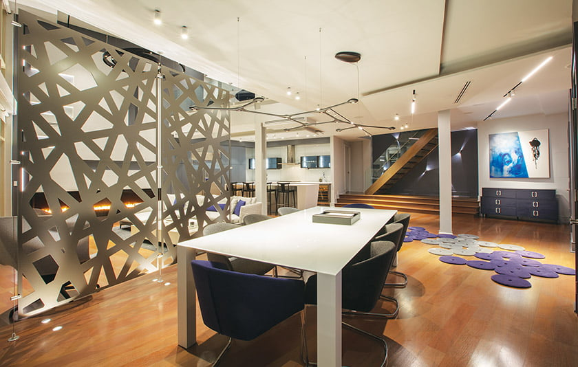 A screen by Móz Designs defines the dining area; linear lights channeled in the ceiling greet visitors near the entry.