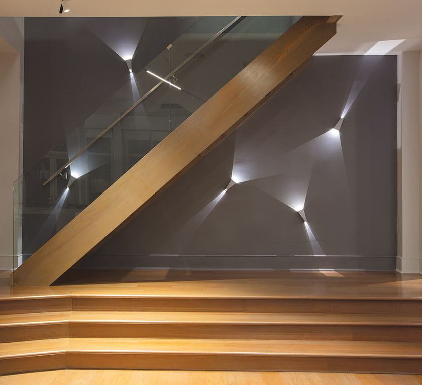 Topix fixtures by Delta Light enliven the staircase wall.