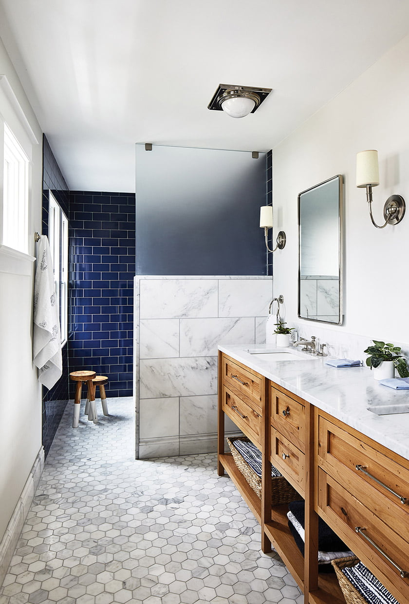 The master bath marries marble and navy-blue ceramic tile with a reclaimed-wood vanity.