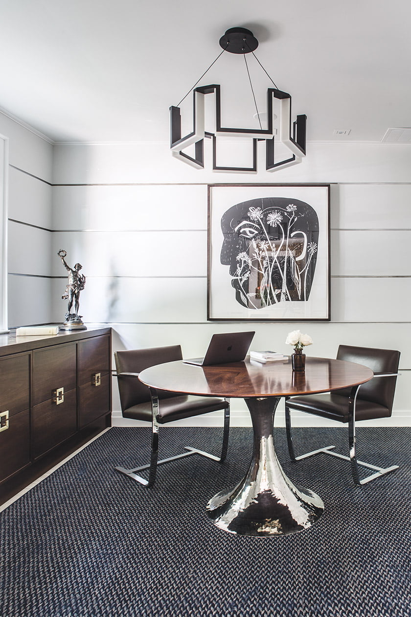 The home office centers on a rosewood table and Modern Forms light fixture.