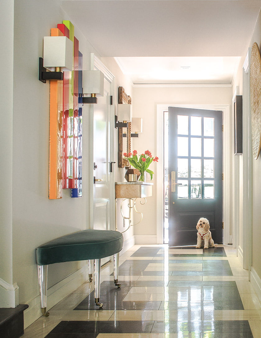 A custom floor motif in porcelain enlivens the entry hall, where the couple's dog, Casey, awaits a walk.
