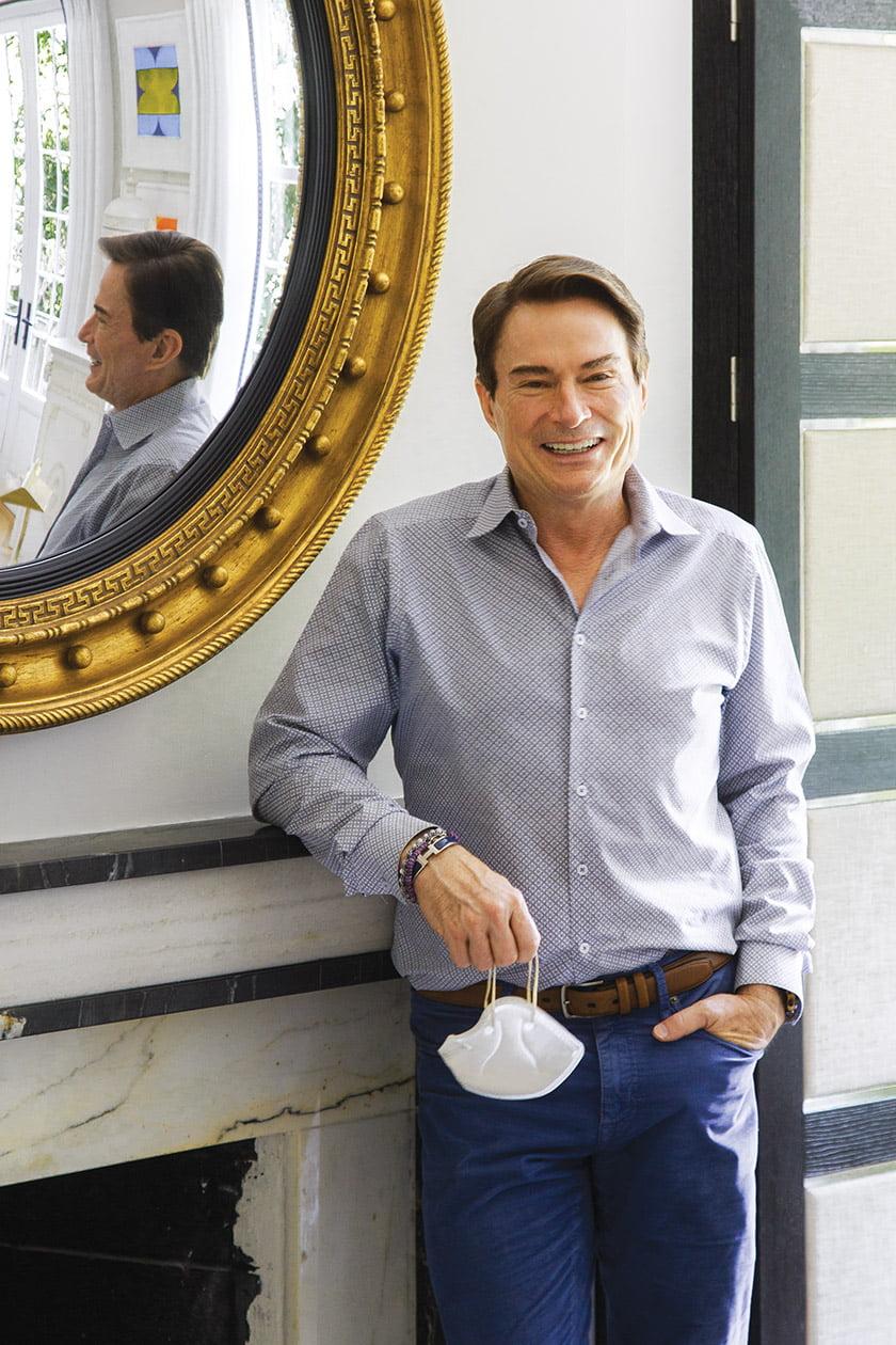 Skip Sroka poses beside a gilt-framed, convex mirror from Carver's Guild.