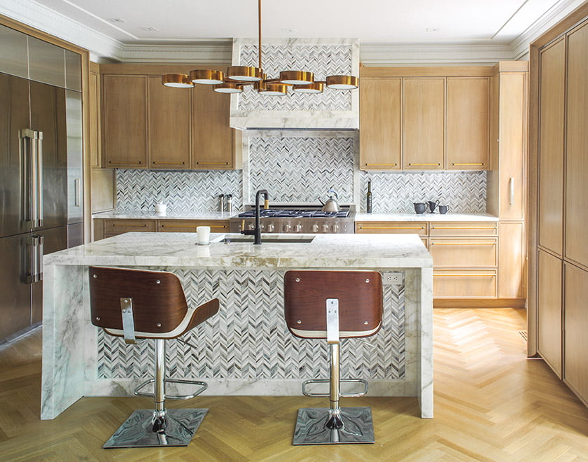 Cool marble surfaces in the kitchen are warmed by bleached-walnut cabinetry and a brass Arteriors fixture.