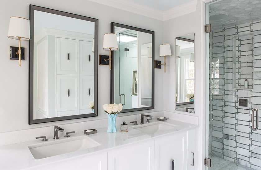 The master bath features custom mirrors from Artisan Framers and a shower enclosure clad in marble mosaic tiles.