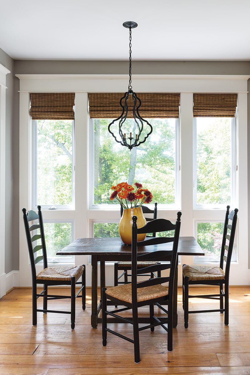 The breakfast nook mixes an antique tavern table with a Visual Comfort chandelier.